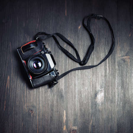 Black retro camera on vintage wood table background. Flat lay.