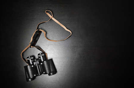Photo of black binoculars on black wood table background. Lot of copy space for your text. Flat lay.