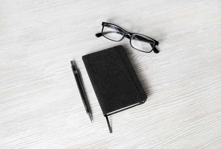 Blank black notebook, glasses and pencil on light wood table background. Template for branding design. Standard-Bild