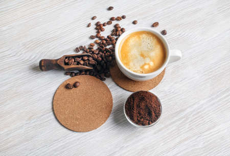 Still life with coffee. Coffee cup, coffee beans, beer coaster and ground powder on light wood table background. Standard-Bild