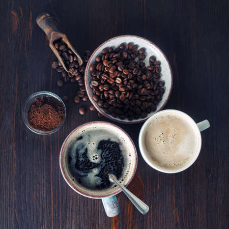 Cups of coffee, coffee beans and ground powder on old wooden background. Top view. Flat lay. Standard-Bild
