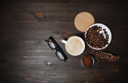 Coffee cup, roasted coffee beans, coffee ground, beer coaster and glasses on wood table background. Flat lay.