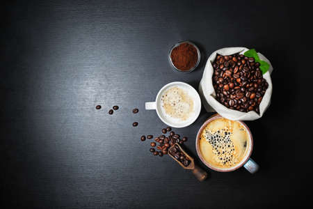 Still life with coffee. Coffee cups and coffee beans in canvas bag on black kitchen table background. Flat lay.