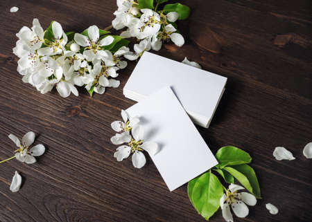 Photo of blank white business cards and flowers on wooden background. Template for ID. Standard-Bild