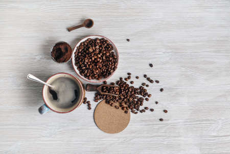Photo of fresh tasty coffee on light wooden background. Coffee cup, coffee beans, ground powder and beer coaster. Top view. Flat lay.
