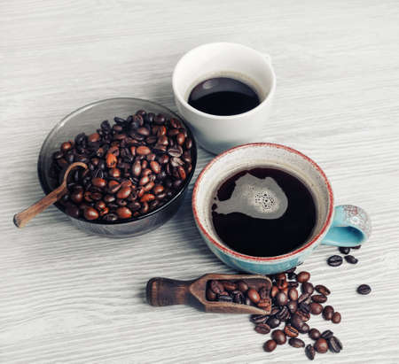 Coffee cups and coffee beans on light wood kitchen table background. Still life with coffee.
