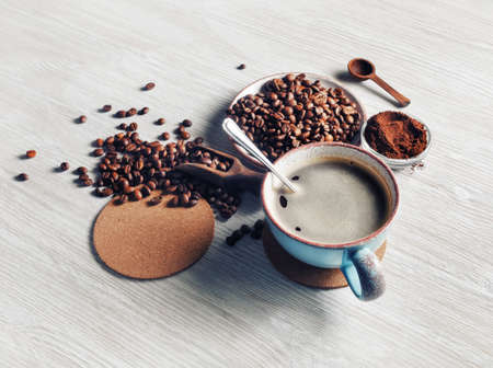 Still life with coffee cup, coffee beans, ground powder and beer coaster on light wooden background.