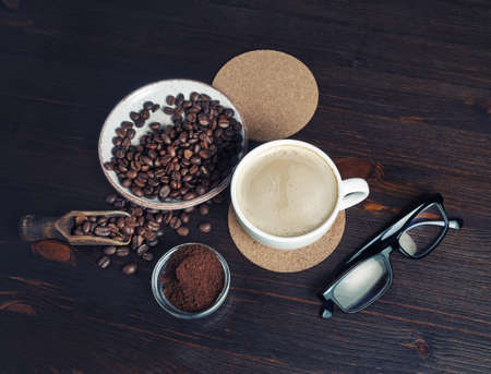 Fresh delicious coffee. Coffee cup, coffee beans, ground powder, beer coaster and glasses on wooden background.