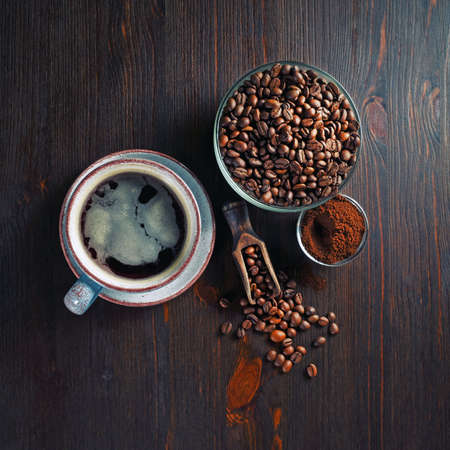 Coffee cup, roasted coffee beans and ground powder on wood kitchen table background. Top view. Flat lay.