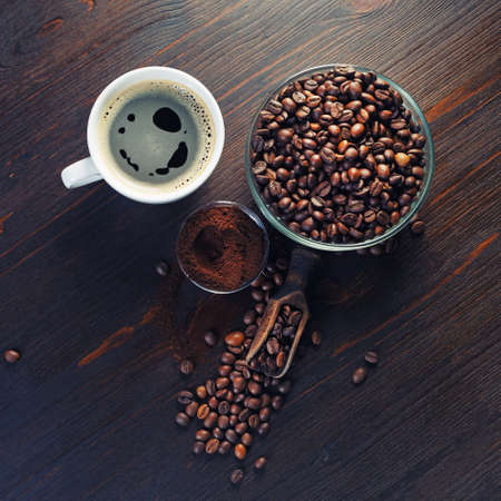 Photo of coffee cup, coffee beans and ground powder on wood kitchen table background. Flat lay.