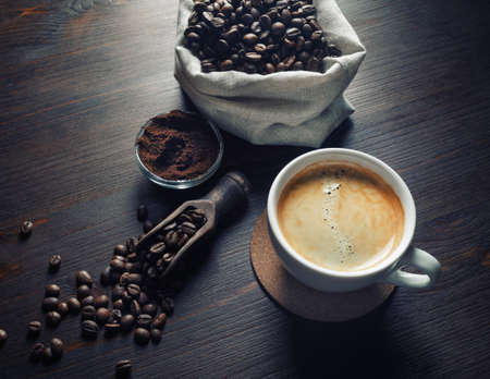 Cup of tasty coffee, coffee beans and ground powder on vintage wooden background.