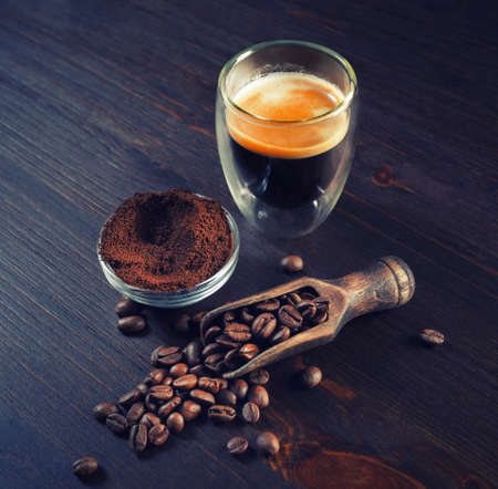 Espresso on vintage wooden kitchen table background. Coffee cup, roasted coffee beans and ground powder.