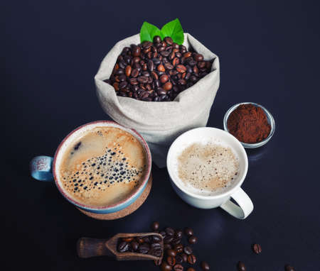 Hot coffee cups and coffee beans in canvas bag and ground powder on black kitchen table background.