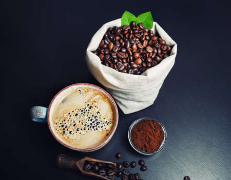 Photo of coffee cup, roasted coffee beans in canvas bag and ground powder on black kitchen table. Standard-Bild