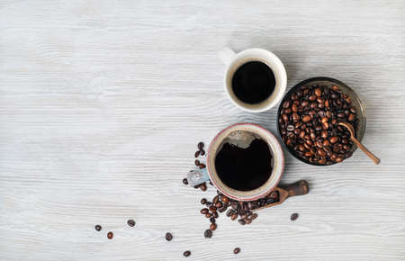 Photo of coffee cups and coffee beans on light wooden background. Copy space for your text. Top view. Flat lay.