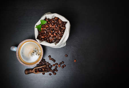 Coffee cup and coffee beans on black wood table background. Copy space for your text. Flat lay.