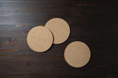 Blank cork beer coasters on wooden background. Responsive design template. Top view. Flat lay.