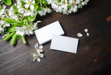 Photo of blank white business cards and flowers on wood table background. Copy space for text.