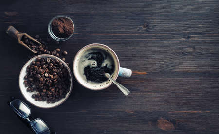 Delicious fresh coffee. Coffee cup, coffee beans, ground powder and glasses on vintage wood table background. Flat lay.