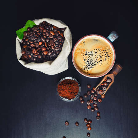 Still life with coffee. Photo of coffee cup and coffee beans in canvas bag on black kitchen wood table background. Flat lay.