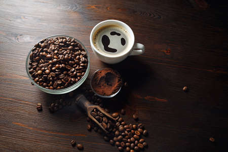 Coffee cup and roasted coffee beans placed on wooden board background.