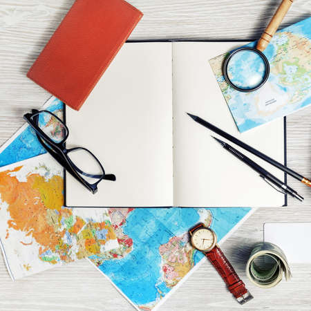 Making travel plan. Map, blank book, magnifier, glasses, notebook, pencils, clock and money. Top view. Flat lay.