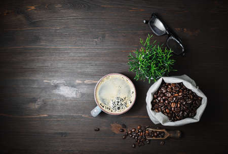 Vintage coffee background, Coffee cup, glasses, plant and roasted coffee beans in canvas bag on wood kitchen table. Flat lay.