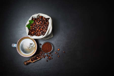 Fresh delicious coffee. Coffee cup and coffee beans in canvas bag and ground powder on black wooden background. Lot of copy space for your text. Flat lay.