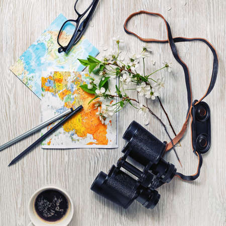 Planning vacation trip with map, binoculars, glasses, pencils, coffee cup and flowers. Travel or vacation concept. Flat lay. Banque d'images