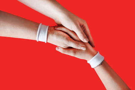Hands with white bracelets unite with eachother as friends greeting on red backgroung.