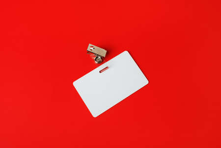 White ID card. Blank security badge on red paper background. Copy space for text.