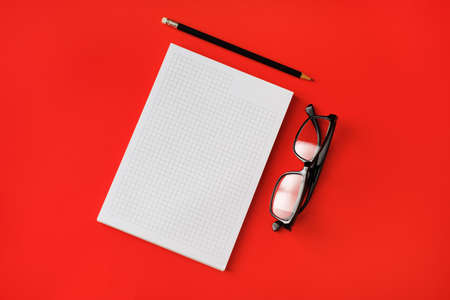 Blank copybook, pencil and glasses on red paper background. Template for branding identity. Top view. Flat lay.