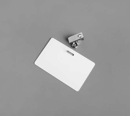 Blank badge on gray paper background. Blank plastic id card. White plastic badge.