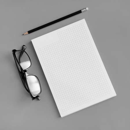 Blank stationery set. Copybook, pencil and glasses on gray paper background. Template for placing your design. Flat lay.