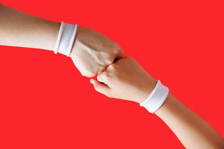 Hands clenched into fists. Fight concept. Two female fists hitting each other on red background.