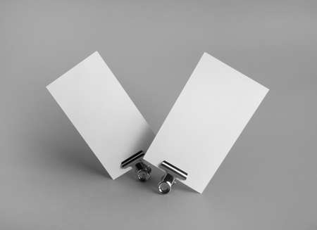Photo of blank business cards and metal binder clips on gray background. Branding ID template.