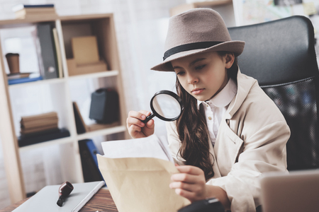Private detective agency. Little girl in cloak and hat is sitting at desk looking at photos with magnifying glass.