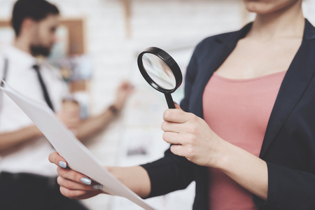Private detective agency. Woman in jacket is posing with paper and magnifying glass, man is looking at clues map. Stock Photo