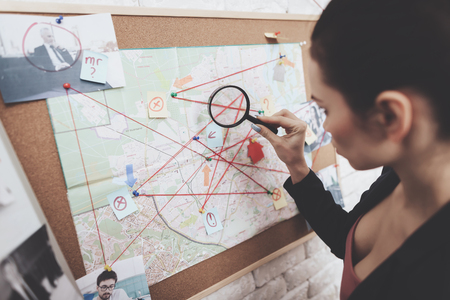 Private detective agency. Woman in jacket is looking at clue map with magnifying glass in office. Stok Fotoğraf
