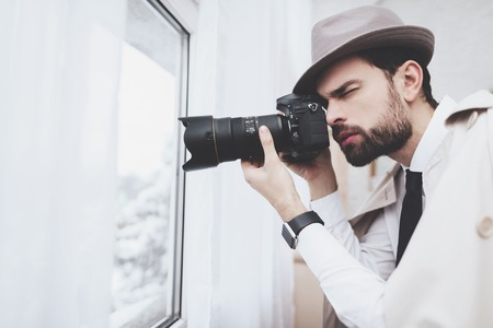 Private detective agency. Man in hat is taking photos in window. Stock Photo