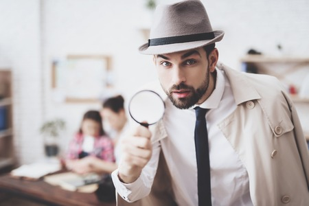 Private detective agency. Man in hat and cloak is posing with magnifying glass, woman is holding her daughter. Stock fotó