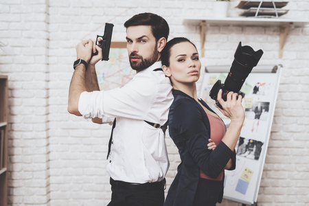 Private detective agency. Woman is posing with camera, man with holster is posing with gun.