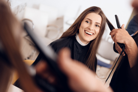 Female hairdresser straighten brown hair to woman using hair iron in beauty salon. Female stylist makes hairstyle for young beautiful woman in hairdressing salon.