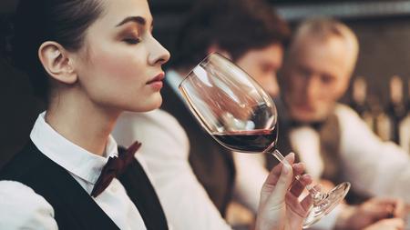 Experienced sommelier woman explores taste of wine in restaurant. Wine tasting. Checking taste, color, sediments of wine.