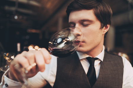 Close up. Young experienced sommelier tasting red wine, poured into glass, closing his eyes. Sommelier enjoys taste of alcoholic beverage. Stock Photo