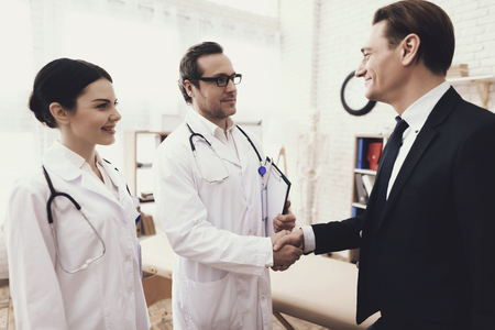Happy businessman shaking hands with doctor who cured ailment. Acknowledgments. Medical examination. Treatment of disease.