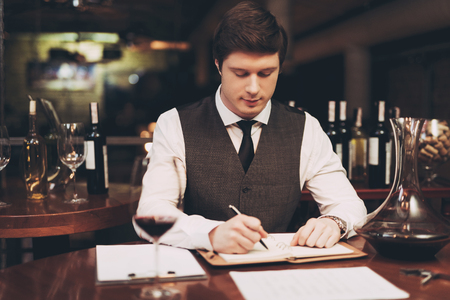Young confident sommelier makes notes in notebook, tasting wine in restaurant. Wine tasting. Confident sommelier checks aging of wine. Stock Photo