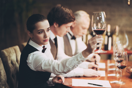 Group of sommeliers make wine card in restaurant. Tasting of elite alcoholic beverages. Experienced sommelier tastes alcoholic beverages in restaurant.
