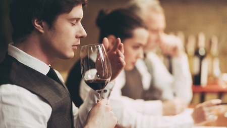 Professional sommelier tastes red wine in restaurant. Sommelier checks aging of wine. Wine tasting.
