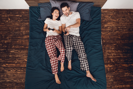 Top view. Young couple in pajamas plays by gamepads in exciting video game, lying on bed in house. Home leisure. Fun at home. Young couple spends time together, playing video games on console.